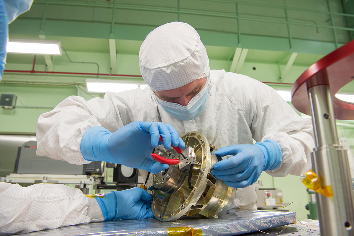 A NASA technician installs an optic reference cube to the HAM mechanism in order to perform alignment measurements