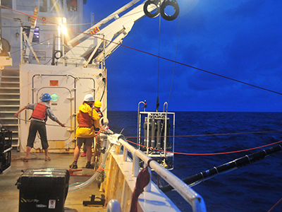 A CTD rosette is retrieved during a night-time sampling session. Credit: NASA/Goddard