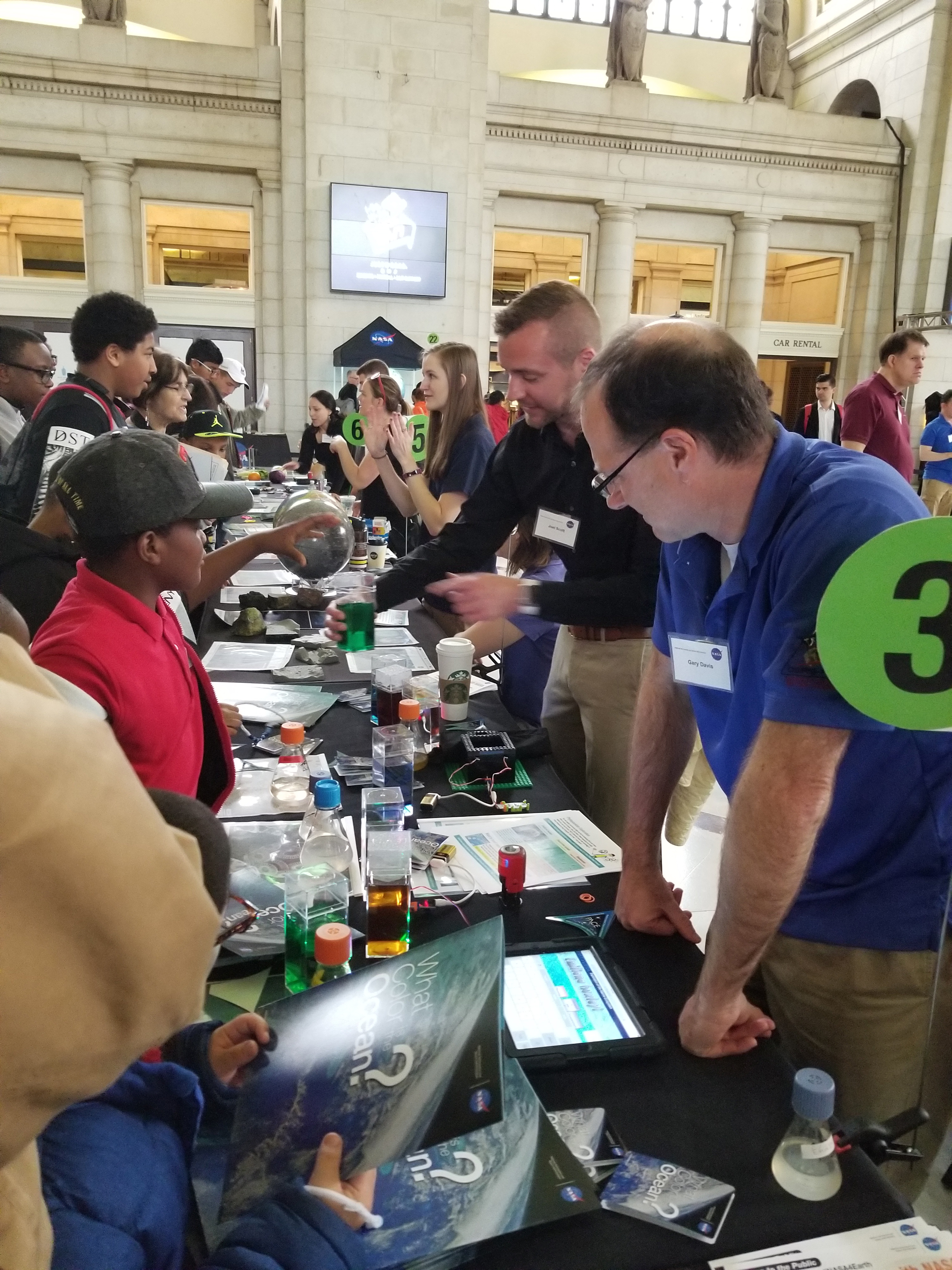 Visitors at the NASA Earth Day Celebration at Union Station (Washington D.C.) check out water with different optical properties while learning about PACE ocean color measurements.