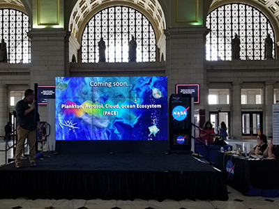 Dr. Jeremy Werdell, PACE Project Scientist, presents a hyperwall talk at the 2018 NASA Earth Day event at Union Station in Washington D.C. Credit: NASA/PACE
