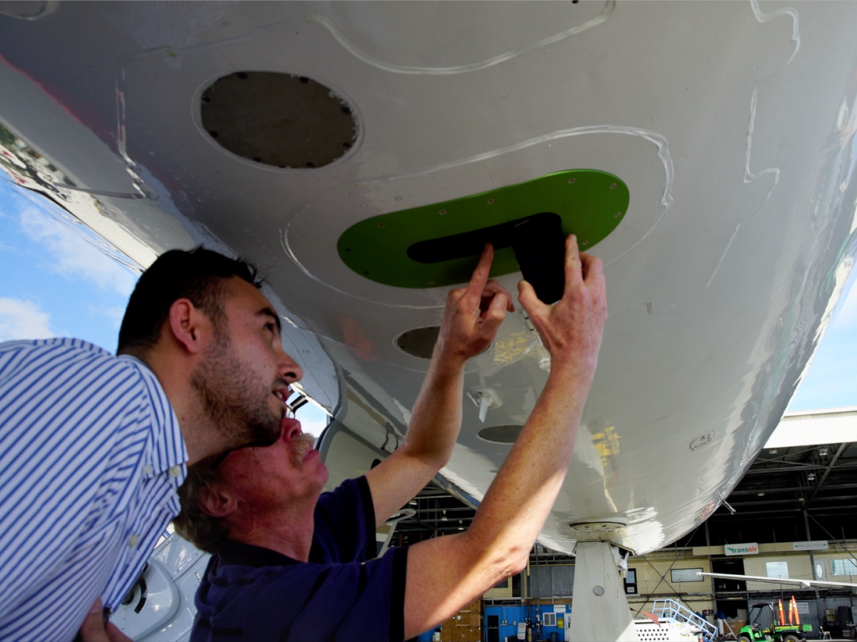 CORAL team members examine PRISM, an airborne instrument that measures the spectra of light