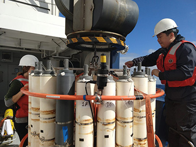 Scientist Yuanheng Xion (University of North Dakota) readies niskin bottles before a test Conductivity, Temperature, and Depth (CTD) cast on a rare cloudless day in the Gulf of Alaska during the EXPORTS cruise. Credit: Abigale Wyatt (PhD student, Princeton University)