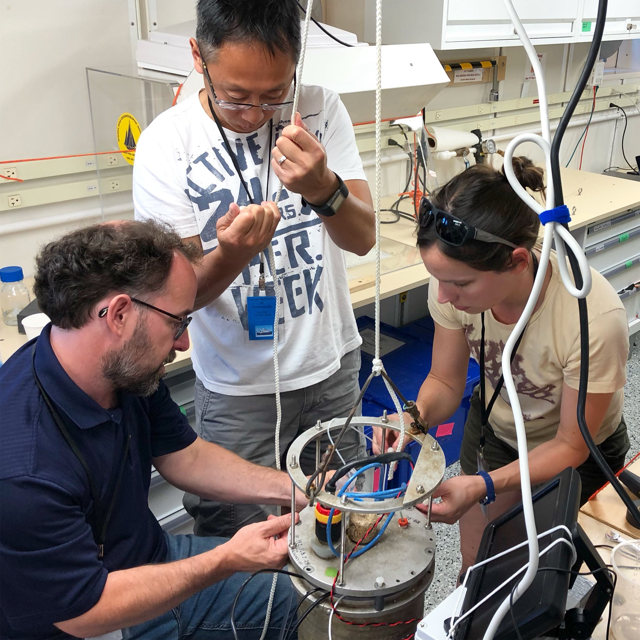 EXPORTS scientists prepare a flow cytometer for operation onboard the R/V <em>Sally Ride</em>.
