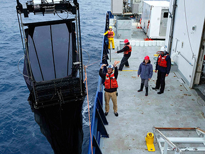 The Multiple Opening/Closing Net and Environmental Sensing System (MOCNESS) is deployed off the bow of the R/V <em>Roger Revelle</em> during the EXPORTS cruise. This specialized net, which includes many different smaller nets that can be used at different depths while being towed behind a vessel, enables researchers to catch plankton throughout the water column. Credit: NASA
