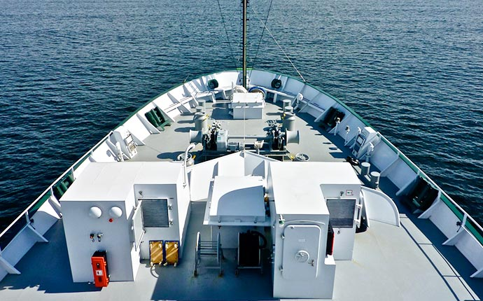 The bow of the R/V <em>Falkor</em> on a clear sailing day.