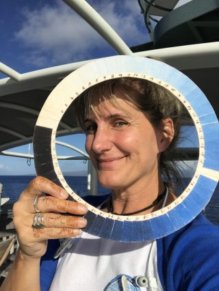 Kirsten Carlson, Sea to Space Particle Investigation Artist at Sea, poses with a replica of a cyanometer, a tool Alexander von Humboldt used to measure the color of the sky.