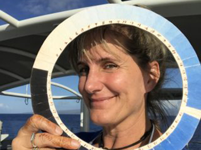 Kirsten Carlson, Sea to Space Particle Investigation Artist at Sea, poses with a replica of a cyanometer, a tool Alexander von Humboldt used to measure the color of the sky. Credit: Schmidt Ocean Institute