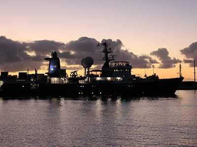 A view of the R/V <em>Falkor</em> at sunset
