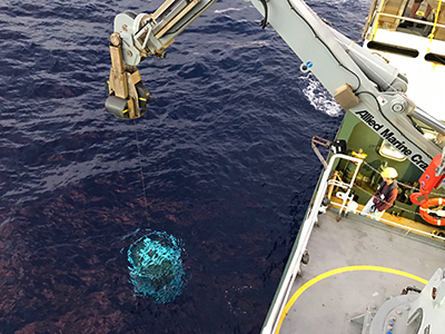 A Conductivity, Temperature and Depth (CTD) sensor is lowered off the side of the R/V <em>Falkor</em> at sunrise.  Credit: Schmidt Ocean Institute