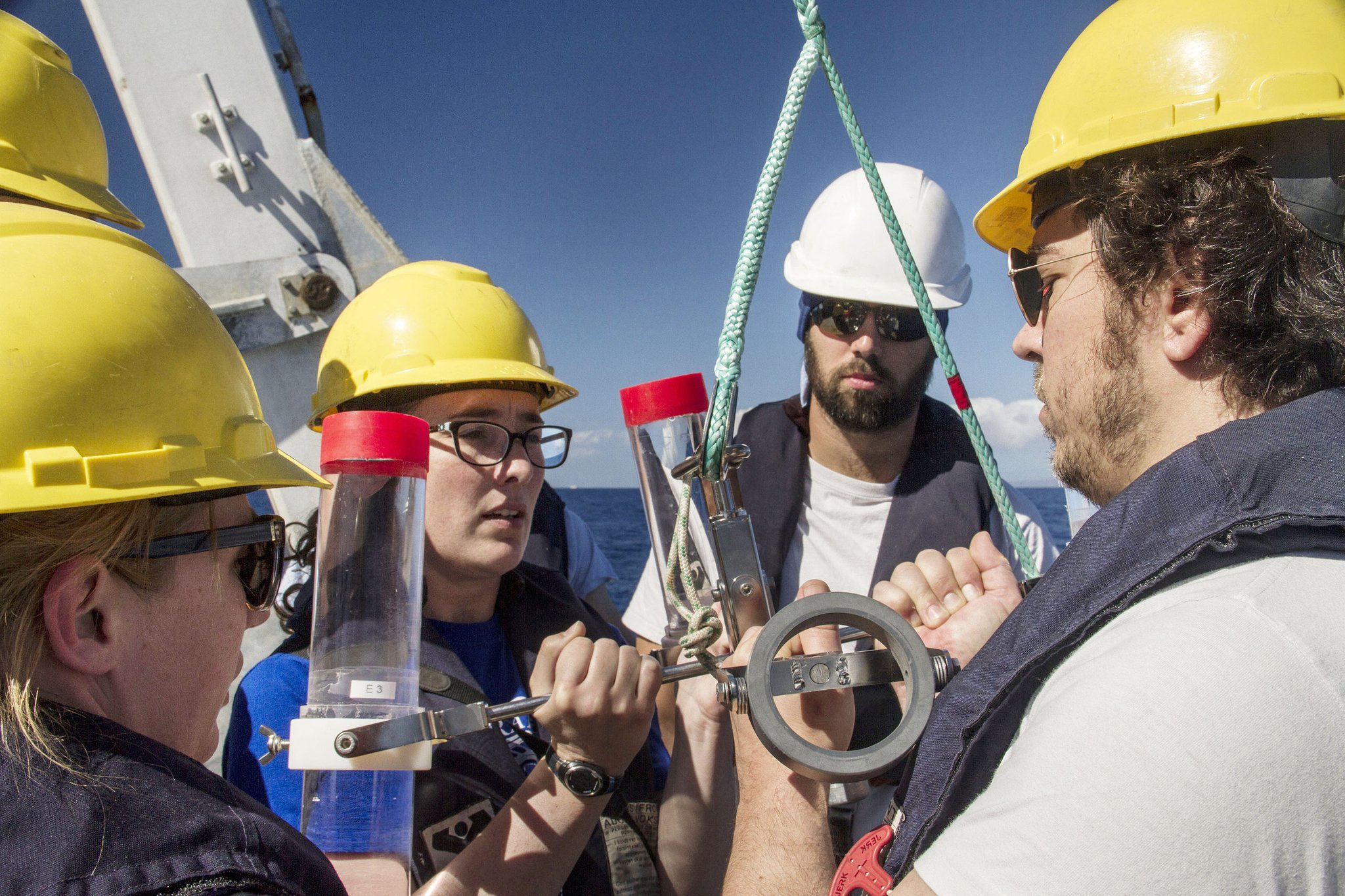 Melissa Omand, Colleen Durkin, Phillipp Guenther and Ben Knorlein make sure that the sediment trap is ready and steady as they prepare to deploy it off the R/V <em> Falkor&#39;s</em> aft deck.