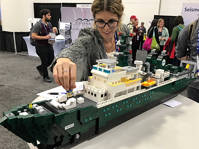 Carlie Wiener (SOI) examines a model of the <em>R/V Falkor</em> made out of legos